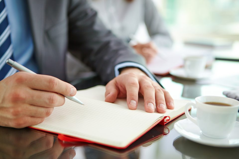 Male hand with pen over empty notebook page during planning work